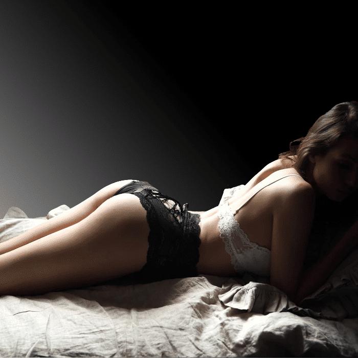 Femme allongée sur un lit avec string gainant